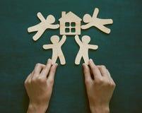 Mãos que guardam homens e a casa de madeira Fotografia de Stock