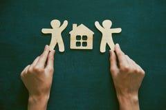 Mãos que guardam homens e a casa de madeira Fotos de Stock Royalty Free
