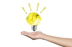 Mãos que guardam a lâmpada de papel da escrita no fundo branco, conce da ideia fotografia de stock royalty free