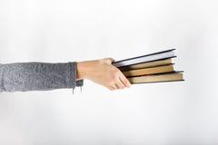 Mãos que guardam livros no fundo branco, fundo da educação Fotos de Stock Royalty Free
