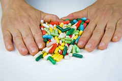 Mãos que guardam muitos comprimidos Imagens de Stock