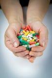 Mãos que guardam muitos comprimidos Fotos de Stock