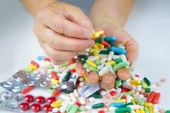 Mãos que guardam muitos comprimidos Fotografia de Stock