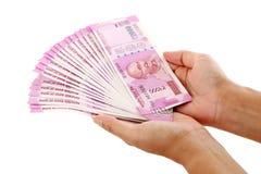 Mãos que guardam 2000 notas da rupia Imagem de Stock