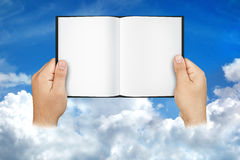 Mãos que guardam nuvens abertas do céu do livro da placa fotografia de stock royalty free