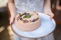 Mãos que guardam o bolo cremoso delicioso Fotografia de Stock
