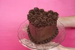 Mãos que guardam o bolo da rosa do coração do chocoalte Imagem de Stock