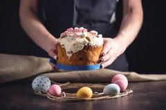 Mãos que guardam o bolo tradicional e ovos coloridos no estilo rústico em um fundo escuro Easter feliz imagens de stock