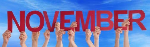 Mãos que guardam o céu azul de novembro da palavra reta vermelha Imagem de Stock