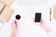 Mãos que guardam o café e o telefone celular foto de stock