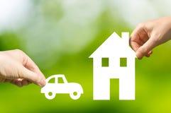 Mãos que guardam o carro e a casa de papel cortados como o símbolo da hipoteca Fotografia de Stock Royalty Free