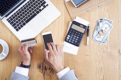 Mãos que guardam o cartão de crédito e contas pagando na tabela fotos de stock royalty free