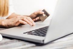 Mãos que guardam o cartão de crédito e que usam o portátil Fotos de Stock