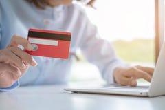 Mãos que guardam o cartão de crédito e que usam o portátil, compra em linha, fazendo o pagamento em linha imagem de stock royalty free