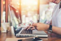 Mãos que guardam o cartão de crédito plástico e que usam o portátil Fotos de Stock Royalty Free