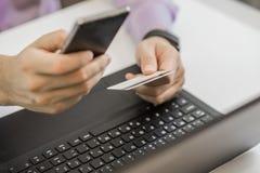Mãos que guardam o cartão de crédito plástico e que usam o portátil Conceito em linha da compra Imagens de Stock