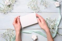Mãos que guardam o cartão de papel vazio em claro - mesa de madeira azul com flores Cartão macio para o dia das mulheres ou de mã fotos de stock