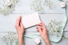 Mãos que guardam o cartão de papel vazio em claro - mesa de madeira azul com flores Cartão macio para o dia das mulheres ou de mã foto de stock royalty free