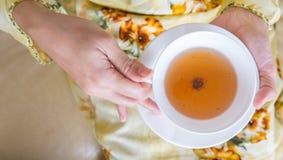 Mãos que guardam o copo do chá IV Fotografia de Stock