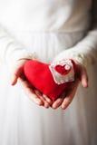 Mãos que guardam o coração vermelho de matéria têxtil Foto de Stock
