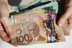 Mãos que guardam o dinheiro canadense foto de stock