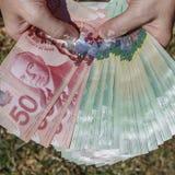 Mãos que guardam o dinheiro canadense fotos de stock