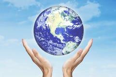 Mãos que guardam o globo com fundo do céu imagens de stock royalty free