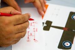 Mãos que guardam o lápis sobre o sheme Foto de Stock Royalty Free