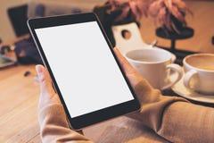 Mãos que guardam o PC preto da tabuleta com a tela branca vazia com os copos de café na tabela de madeira no café moderno Fotografia de Stock