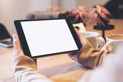 Mãos que guardam o PC preto da tabuleta com a tela branca vazia com os copos de café na tabela de madeira no café moderno Fotografia de Stock Royalty Free