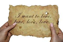 Mãos que guardam o pergaminho velho com as palavras 'que eu quero amar, amor, amor ` fotografia de stock royalty free