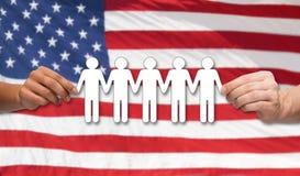 Mãos que guardam o pictograma dos povos sobre a bandeira americana Foto de Stock Royalty Free