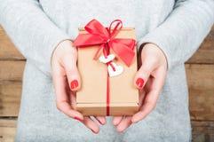 Mãos que guardam o presente na caixa de kraft em um fundo de madeira O concentrado Fotos de Stock Royalty Free