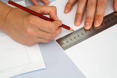 Mãos que guardam o ruller e o lápis Fotos de Stock Royalty Free