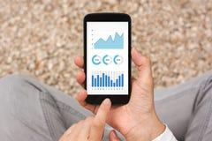Mãos que guardam o smartphone com elementos dos gráficos e das cartas no scre Imagem de Stock