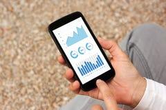 Mãos que guardam o smartphone com elementos dos gráficos e das cartas no scre Imagens de Stock Royalty Free