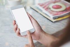 Mãos que guardam o telefone celular branco com a tela branca vazia no café moderno Imagens de Stock Royalty Free