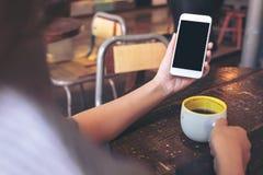 Mãos que guardam o telefone celular branco com a tela preta vazia do desktop e uma xícara de café na tabela de madeira no café Foto de Stock