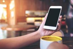 Mãos que guardam o telefone celular branco com a tela preta vazia do desktop e uma xícara de café na tabela de madeira no café Fotos de Stock
