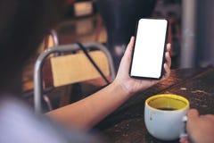 Mãos que guardam o telefone celular branco com a tela preta vazia do desktop e uma xícara de café na tabela de madeira no café Fotos de Stock Royalty Free