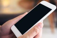 Mãos que guardam o telefone celular branco com a tela preta vazia do desktop no café Fotos de Stock Royalty Free