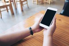Mãos que guardam o telefone celular branco com a tela preta vazia na tabela de madeira no café Fotografia de Stock