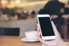 Mãos que guardam o telefone celular branco com a tela preta vazia com os copos de café na tabela de madeira no restaurante Imagens de Stock Royalty Free