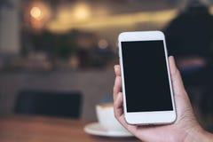 Mãos que guardam o telefone celular branco com a tela preta vazia com os copos de café na tabela de madeira no restaurante Imagens de Stock