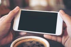 Mãos que guardam o telefone celular branco com a tela preta vazia para olhar e jogar jogos com uma xícara de café Fotos de Stock Royalty Free