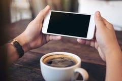 Mãos que guardam o telefone celular branco com a tela preta vazia para olhar e jogar jogos com uma xícara de café na tabela de ma Foto de Stock Royalty Free