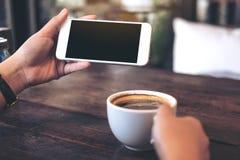 Mãos que guardam o telefone celular branco com a tela preta vazia para olhar e jogar jogos com uma xícara de café na tabela de ma Imagens de Stock Royalty Free