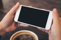 Mãos que guardam o telefone celular branco com a tela preta vazia para olhar e jogar jogos com uma xícara de café na tabela de ma Imagens de Stock