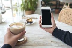 Mãos que guardam o telefone celular branco com a tela preta vazia com uma xícara de café e um petisco na tabela no café Fotos de Stock