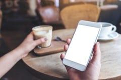 Mãos que guardam o telefone celular branco com a tela vazia do desktop e um vidro do café na tabela de madeira no café Imagem de Stock Royalty Free